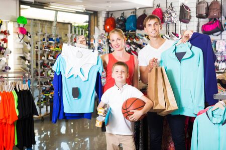 Young family of three picking various clothing in sport department