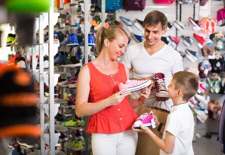 happy  smiling family of three choosing new sport shoes in sport supermarket. Focus on woman