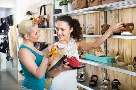 Ttwo glad beautiful young women selecting a shoes and chatting among shelves. Focus on both persons
