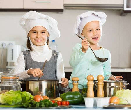 Two little european  girls preparing vegetables and smiling indoors