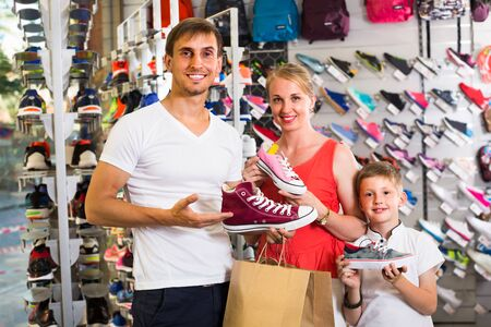 joyful smiling parents with schoolboy son buying new sport shoes in sport supermarket