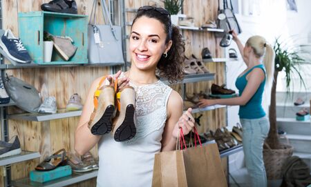 portrait of cheerful girl showing a chosen pair of shoes while her friend still choosing
