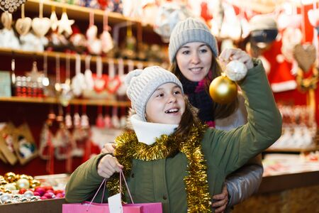 Young girl and her mother are choosing decorations for Christmas tree in the market outdoor. Archivio Fotografico - 129806502