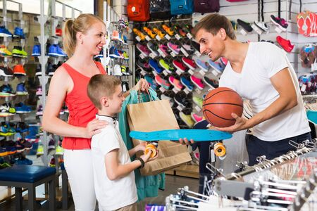 cheerful smiling parents choosing skateboard for schoolboy son in sport department