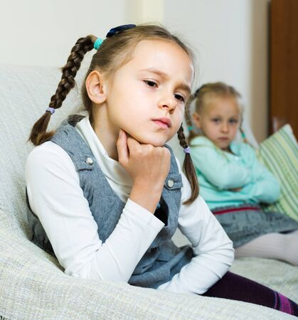 Offended little girl sitting apart of little sister after conflict at home Stock fotó