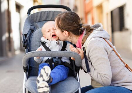 Happy positive  female and her toddler are standing on the street after shopping in time walking. 写真素材