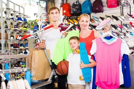 Positief jong gezin van drie dat verschillende kleding plukt op de sportafdeling Stockfoto