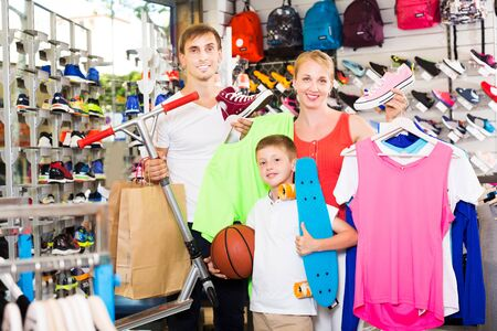 Positive young family of three picking various clothing in sport department Stok Fotoğraf