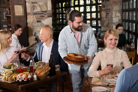 Smiling bearded waiter bringing ordered dishes to guests in cozy country restaurant 写真素材