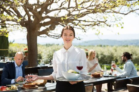 Hospitable young female owner of cosy country restaurant in open air meeting guests with serving tray in hands