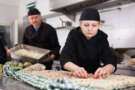 Professional female cook engaged in preparation of cannelloni rolls from fresh pasta sheets and minced meat