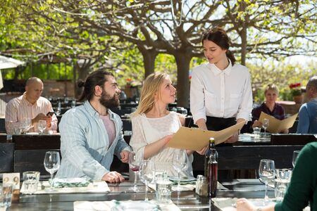 Charming young waiter and couple at open-air restaurant summer