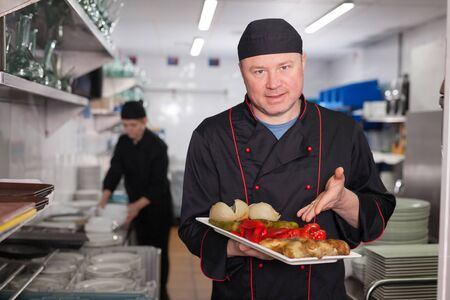 Portrait of confident chef working in restaurant kitchen, showing right off stove dish