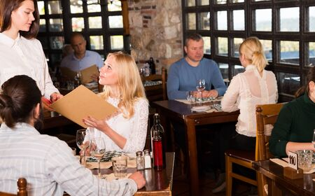 Guests of the country restaurant discuss menu with waitress