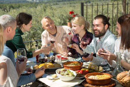 Company of six spends time at lunch in a open-air terrace