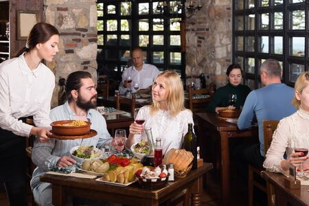 Young attractive waitress bringing delicious meals to visitors of cosy rustic style restaurant