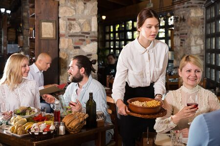 Young female waiter serving country restaurant guests