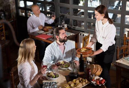 Hospitable young female owner of rustic restaurant serving traditional meals to guests