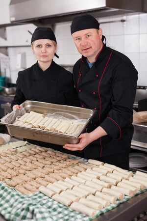 Portrait of two professional cooks standing in restaurant kitchen, holding baking tray with raw cannelloni stuffed with mincemeat