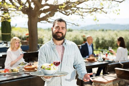 Polite bearded waiter with serving tray welcoming on terrace of country restaurant Stockfoto