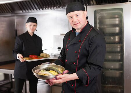Smiling chef presenting delicious cooked fish dish in restaurant kitchen, ready to serve it to guests