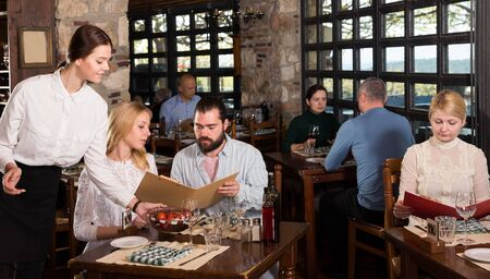 Polite young waitress showing menu card to couple, recommending dishes in cosy country restaurant Stock Photo