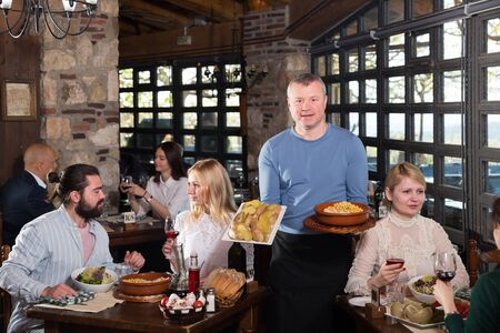 Male waiter carrying order for visitors in country restaurant Stock Photo