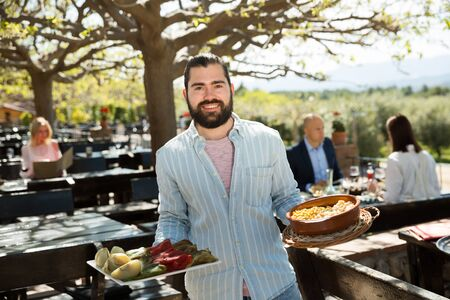 Adult beard waiter who is standing with order at country outdoor restaurant