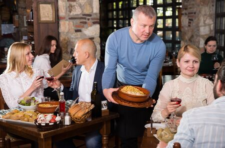Male waiter carrying order for visitors in country restaurant Stock Photo - 129809019