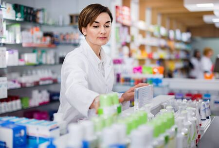 Young diligent female pharmacist arranging displayed assortment in pharmacy Reklamní fotografie