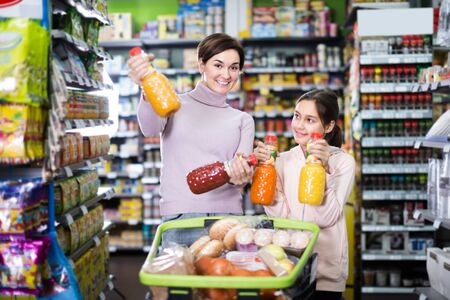 smiling mother with daughter choosing refreshing beverages on shelves in supermarket