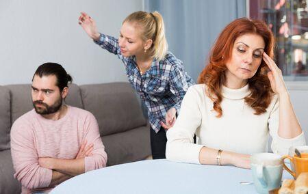 Husband and wife quarrelling indoors, senior mother taking it hard Stock fotó
