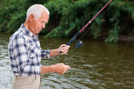 Portrait of mature man standing and fishing at river beach on summer day 写真素材