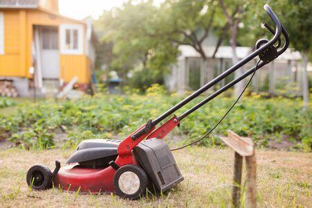 Grass mower stands on green lawn in summer garden Stock fotó