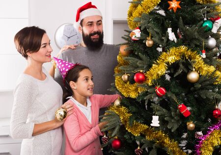 Parents and daughter putting decorations on Christmas tree at home Archivio Fotografico - 129809047