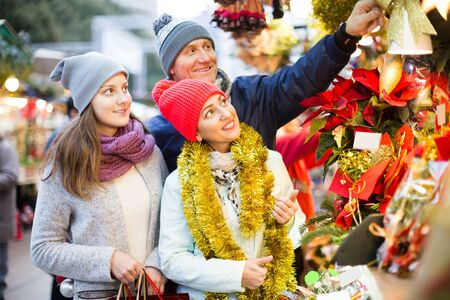mature mother, father and teen girl buying red Euphorbia and  floral decorations  at Christmas fair outdoors
