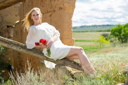 Sexy young female  in white dress  posing on tree trunk with poppy  flowers in hands in countryside