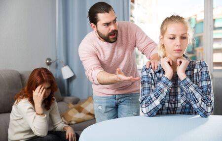 Portrait of sad young girl having conflict with boyfriend in home interior