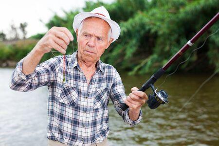 Elderly man standing at riverside and testing bait on fishing hook line 写真素材 - 129809101
