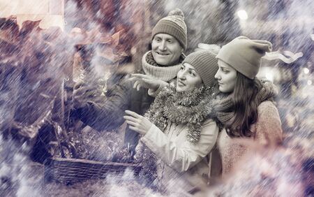 Happy european family of three with teenage girl choosing  floral decorations  at market. Shallow depth of focus