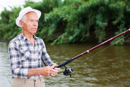 Positive adult man with rod relaxing and enjoying fishing by lakeside 写真素材