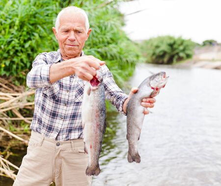 Satisfied mature fisherman showing fresh catch two trouts at riverside on summer