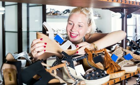 Portrait of beautiful young woman looking after summer pair of shoes in store