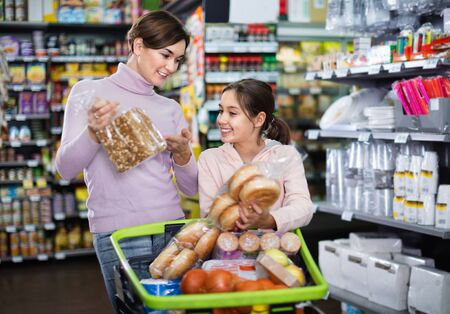Young cheerful positive woman customer with girl looking for tasty bread in supermarket