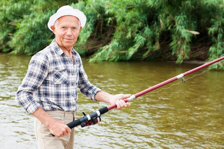 Cheerful adult fisherman standing with angling rod and fishing at sunny summer day 写真素材