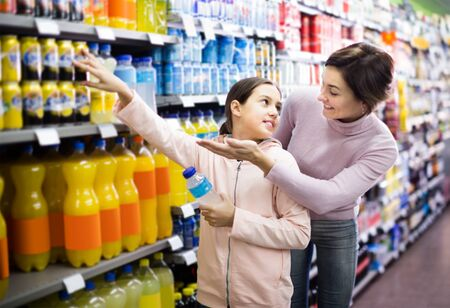 smiling woman with daughter choosing refreshing beverages on shelves in supermarket