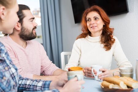 Portrait of mature woman with daughter talking at table with cup of tea