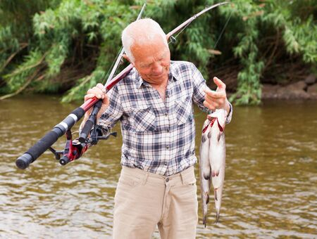 Senior male fisher examining catch fish while angling at lakeside on summer day 写真素材 - 129809176