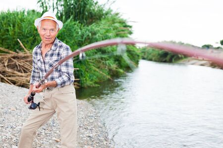 Mature fisherman standing on riverside and going to pull out catch fish 写真素材 - 129809190