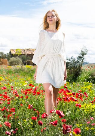 Young woman  in white dress walking through a poppies plant outdoor